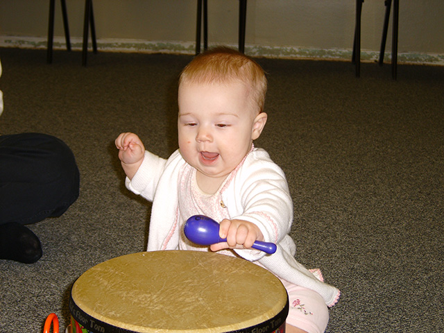 Happy child playing drum with maraca